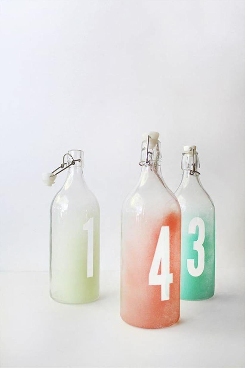 botellas de vidrio para marcar las mesas de la boda