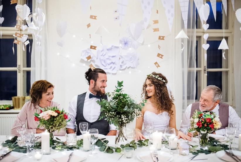 pareja con familia en mesa recepción de boda