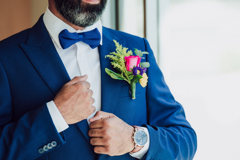 traje de novio azul con botonnier de rosa y moño azul