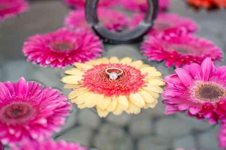 anillo de compromiso con diamante sobre flor amarilla y fucsia