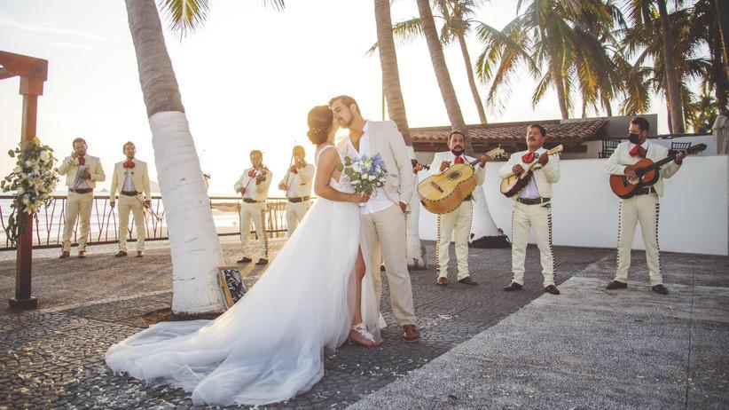 novios se besa mientras mariachis tocan en la boda