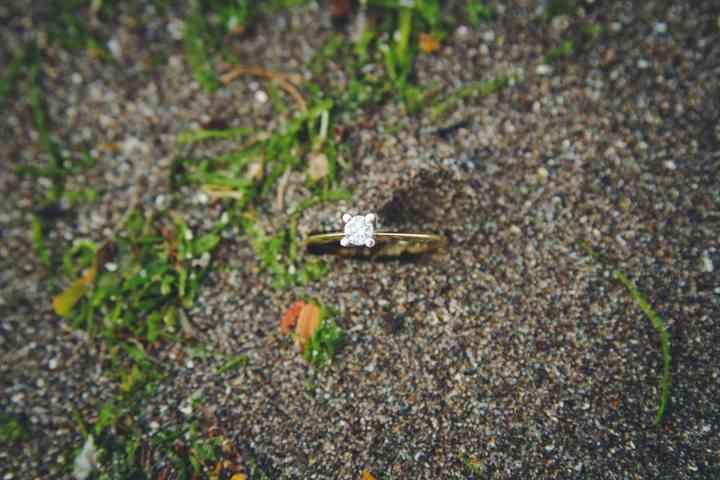 anillo de compromiso solitario sobre arena