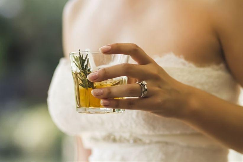 novia en su boda con bebida en la mano