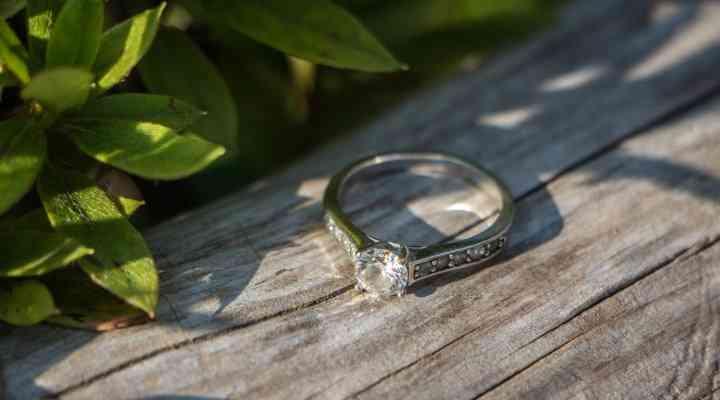 foto de anillo de compromiso solitario con diamantes en superficie de madera