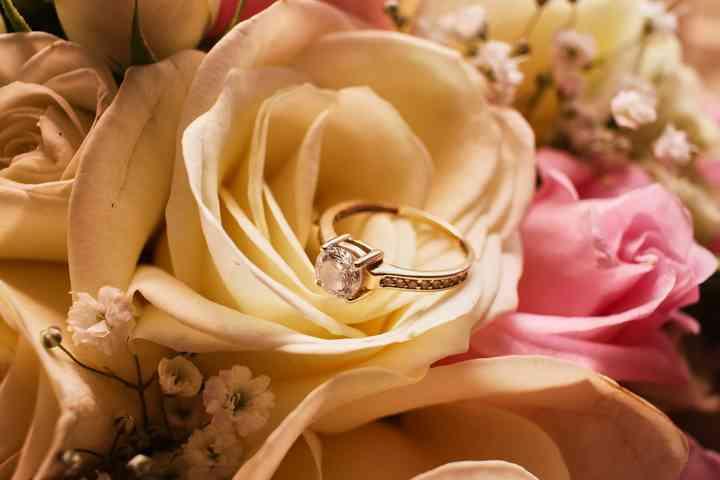 foto anillo de compromiso sobre rosa blanca del ramo de novia